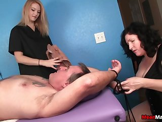 Tattoed man lays on his up to the fullest extent a finally two sluts pleasure his cock